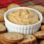 Barbecue flavored hummus in white bowl surrounded by crackers