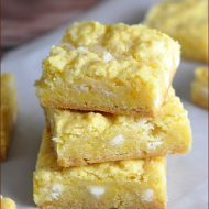 These Gooey Bars get a triple dose of lemon, from lemon cake, lemon zest, and lemon curd. Moist, chewy, and amazing!