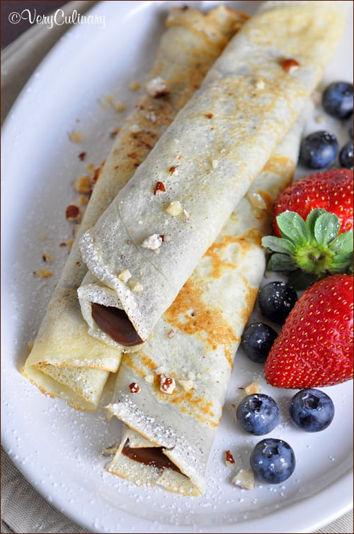 Crepe-like pancakes filled with Nutella and fruit, then rolled up and sprinkled with powdered sugar. Pancakes have never been so good!