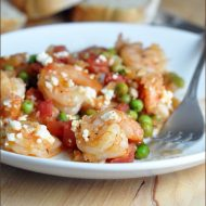 Shrimp is baked in a tangy lemon and wine reduction, sweet tomatoes and peas, and salty feta. Serve on its own or with sliced bread!