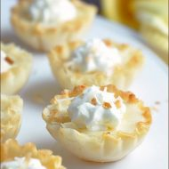 Small fillo shells are filled with a lemon custard and topped with whipped cream and toasted coconut!
