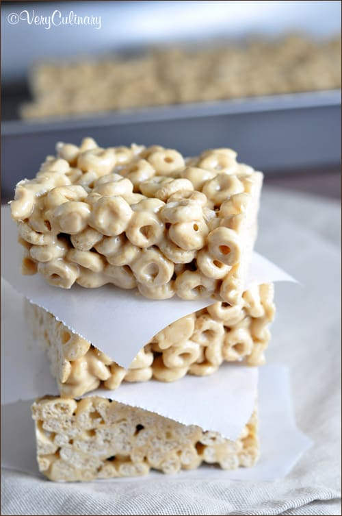 Marshmallow cereal treats made with Honey Nut Cheerios, Biscoff cookie butter spread, and white chocolate chips.