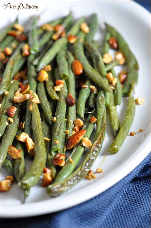 Fresh green beans are roasted with seasonings until crisp tender, then topped with Sriracha Almonds for a little added kick! #ad