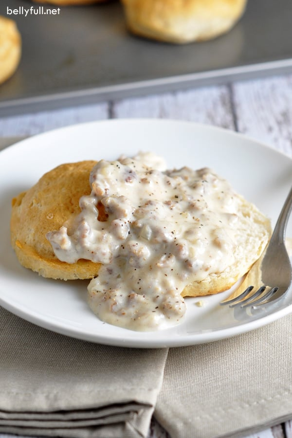 homemade biscuits with sausage gravy on plate with fork
