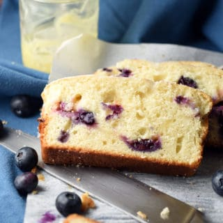stacked slices of lemon blueberry bread with jar of lemon curd and knife on parchment paper