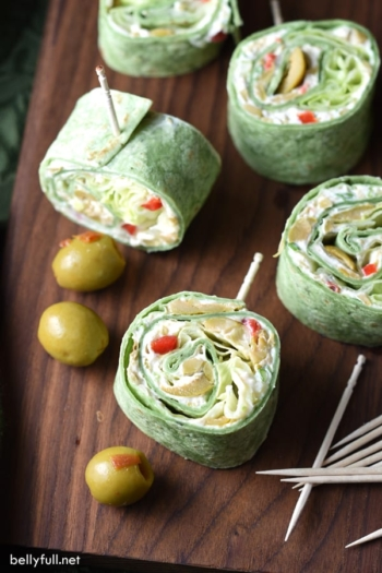 In these Olive Pinwheels, spinach flavored flour tortillas are coated with an olive and cream cheese spread, topped with scallions and lettuce, for an easy crowd-pleasing appetizer, snack, or light lunch!