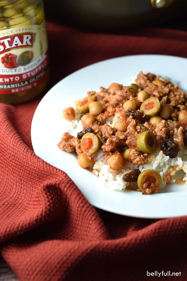This Ground Turkey Picadillo is simmered in tomato sauce, olives, beans, raisins, and spices. It's the perfect mixture served over rice, on rolls, or as taco filling!