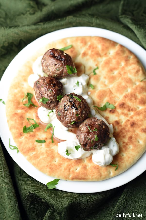 Mediterranean spiced meatballs are grilled and then served on flatbread with a light and refreshing yogurt-mint sauce
