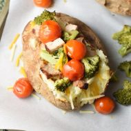 Grilled baked potato stacked high with seasoned pork, broccoli, cherry tomatoes, and gooey cheese!