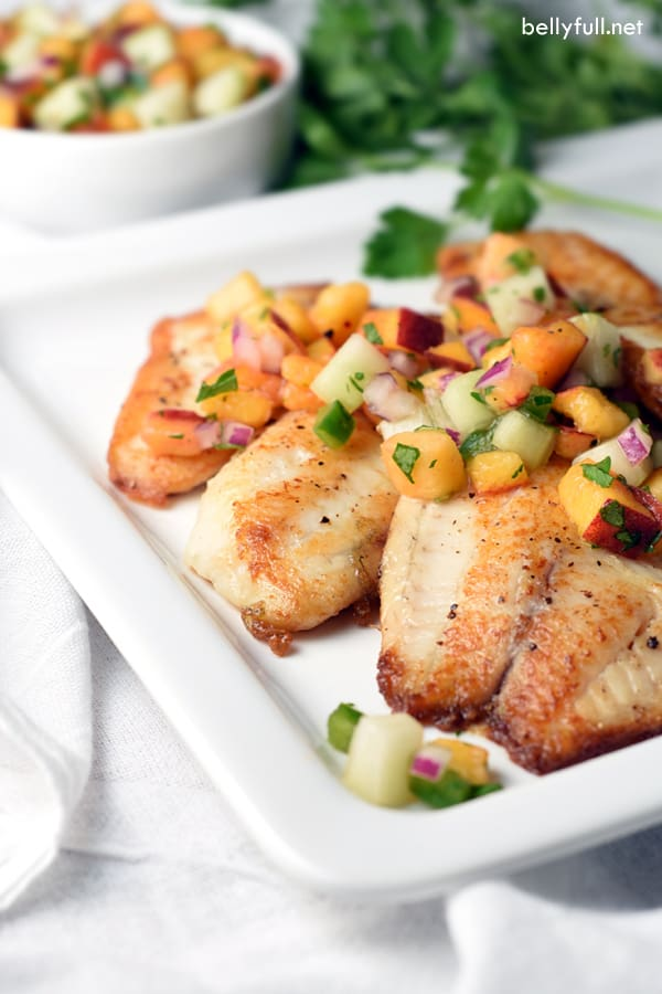 Pan Seared Tilapia fillets are topped with a fresh, bright, and simple peach and cucumber salsa. Delicious 30 minute meal!
