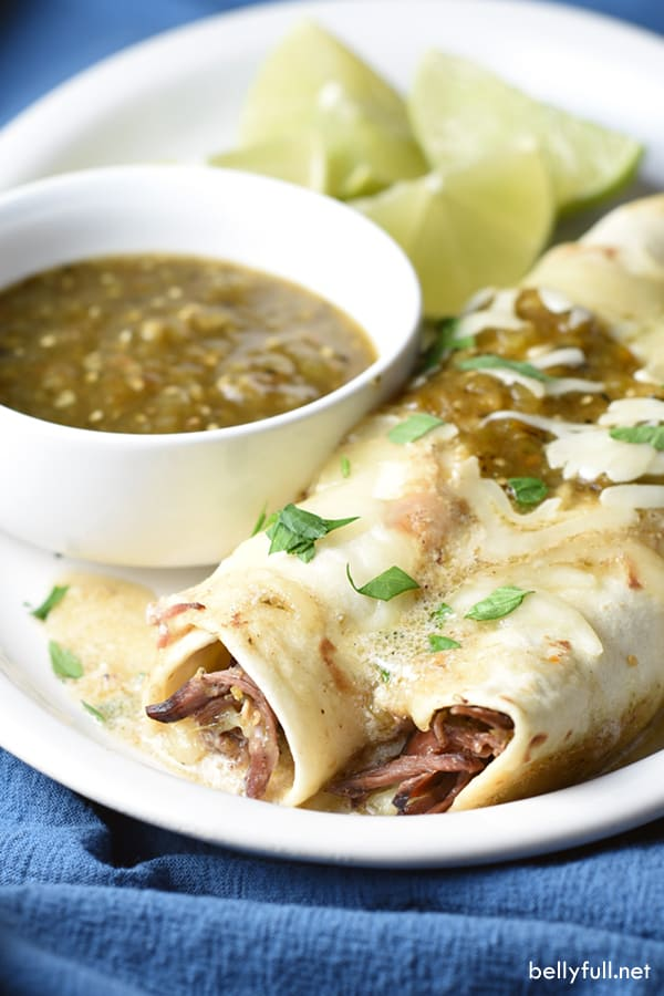This delicious recipe for Salsa Verde Beef Enchiladas is bursting with authentic flavors and sure to be a crowd pleaser!