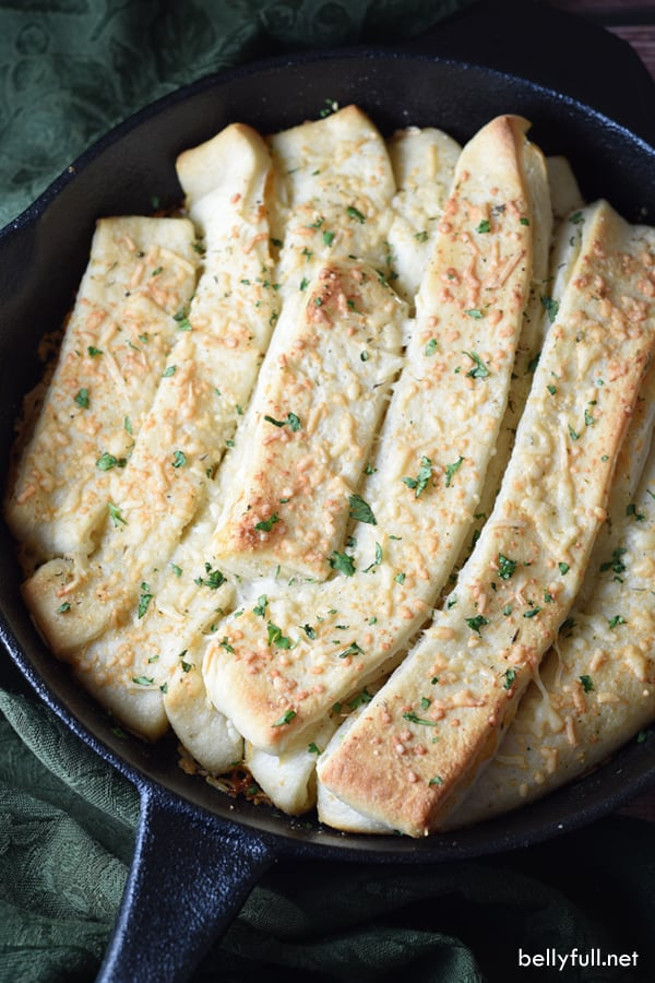 Easy homemade breadsticks with butter, garlic, herbs, and mozzarella. Then sprinkled with parmesan and baked in a cast iron skillet. Great with soup, dipped in marinara, or all on their own!