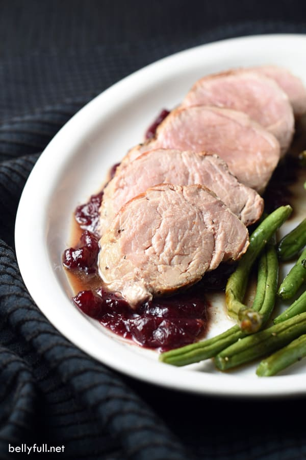 Pork tenderloin is marinated in garlic and cracked black pepper seasonings, then topped with a cranberry-pomegranate sauce and served with roasted green beans. Wonderful and easy complete meal!