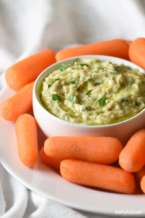 white bean dip in a bowl surrounded by baby carrots