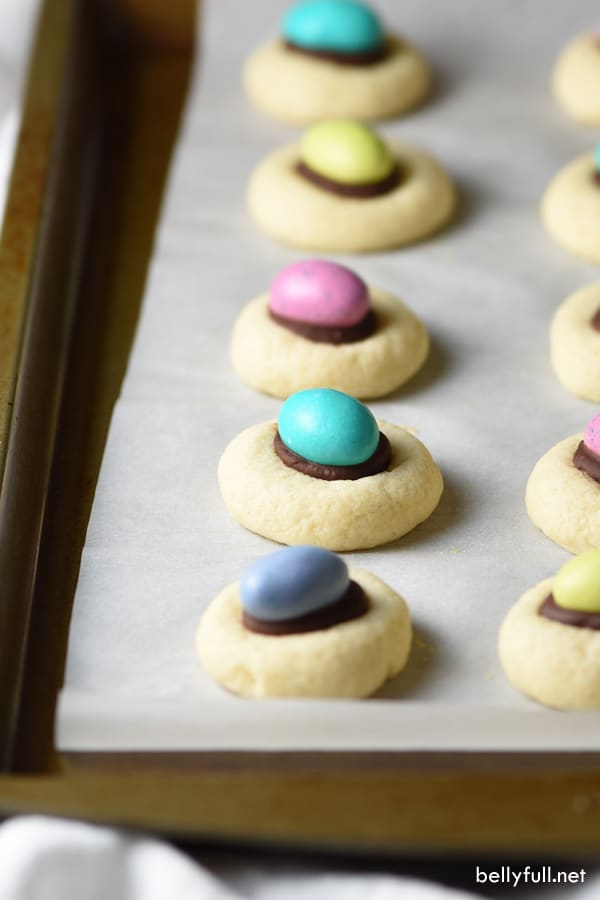 These thumbprint cookies are light and flaky with a chocolate ganache center, top with an M&M egg for a cute Easter treat!