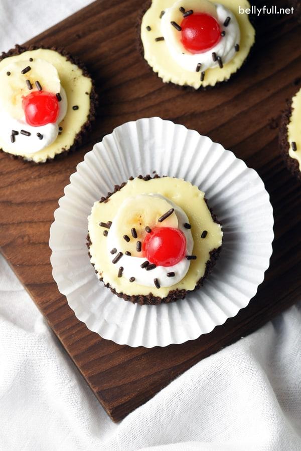 overhead of mini banana split cheesecakes in white muffin liner