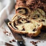 This Chocolate Challah Bread is a cross between Challah and Babka. A sweet yeast dough that is doubled and twisted, filled with a ganache, sprinkled with a streusel topping, basted with butter, then baked in a loaf pan to perfection!