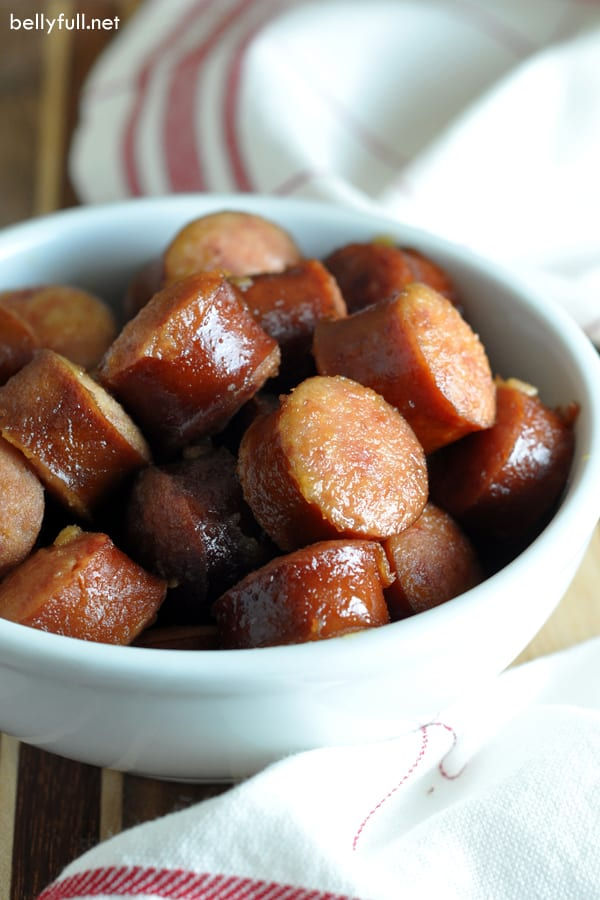 Kielbasa pieces coated in apple sauce in white bowl