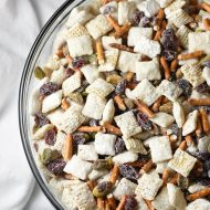 15-minute Chex Mix Muddy Buddies with a Christmas holiday flair, including white chocolate, powdered sugar, pretzels, craisins, and pistachios!