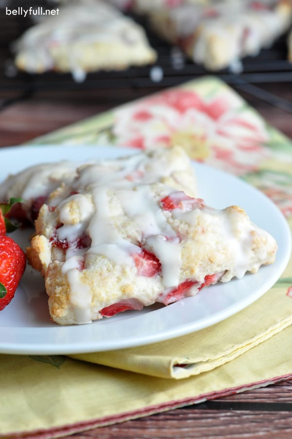 strawberry scones with icing on a white plate