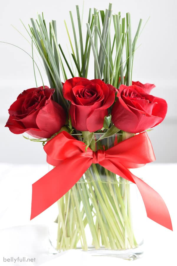 red roses in a clear vase with greenery