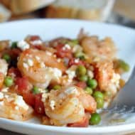 Baked Shrimp with Tomatoes and Feta - shrimp is baked in a tangy lemon and wine reduction, sweet tomatoes and peas, and salty feta. Serve on its own or with sliced bread!