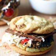 These Tropical S'mores are a fun twist on a classic! S'mores with white chocolate macadamia nut cookies, grilled pineapple, maraschino cherries, chocolate, and toasted coconut. So good!