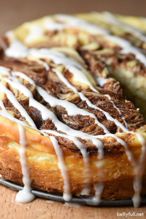 Cinnamon Roll Cheesecake with icing drizzled down sides