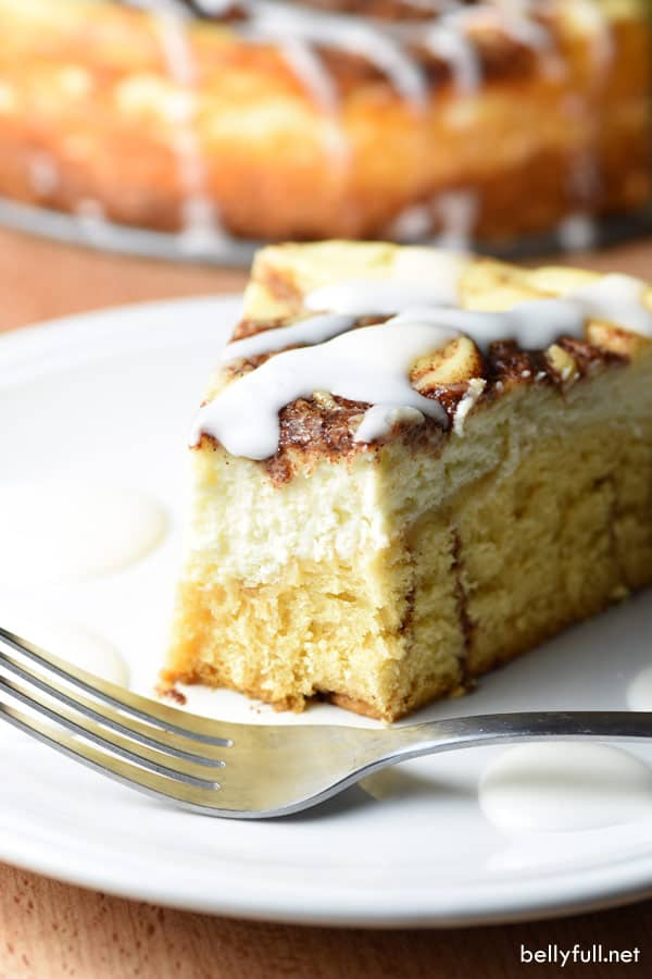 slice of Cinnamon Roll Cheesecake with bite on white plate with fork