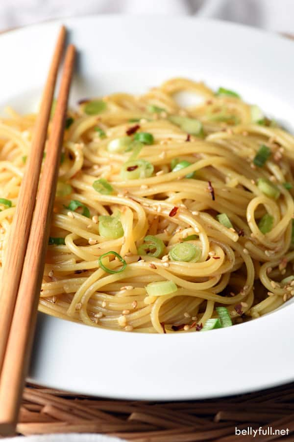 sesame noodles in white bowl with chopsticks on top