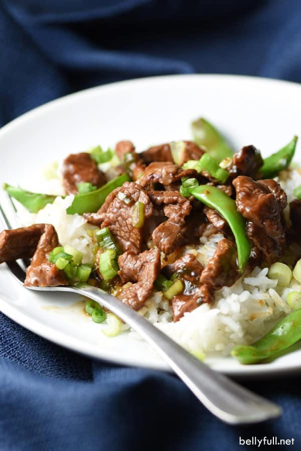 Stir Fry Beef with Snow Peas over rice on white plate