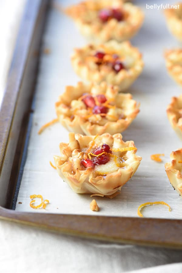 picture of small fillo shells filled with brie cheese, ham, and pomegranate seeds