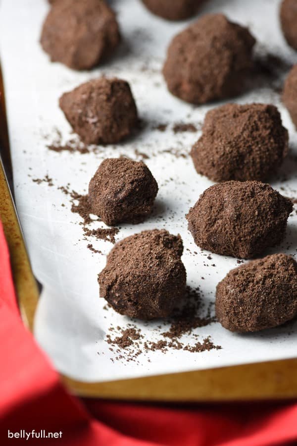rice krispie treats formed into lumps of coal on a parchment paper lined baking sheet
