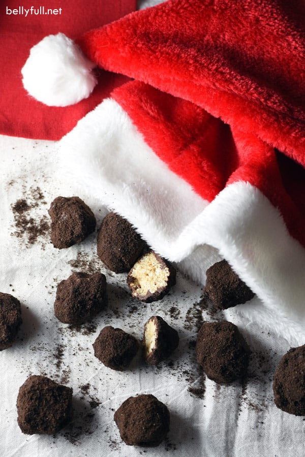 rice krispie treats formed into lumps of coal with santa hat