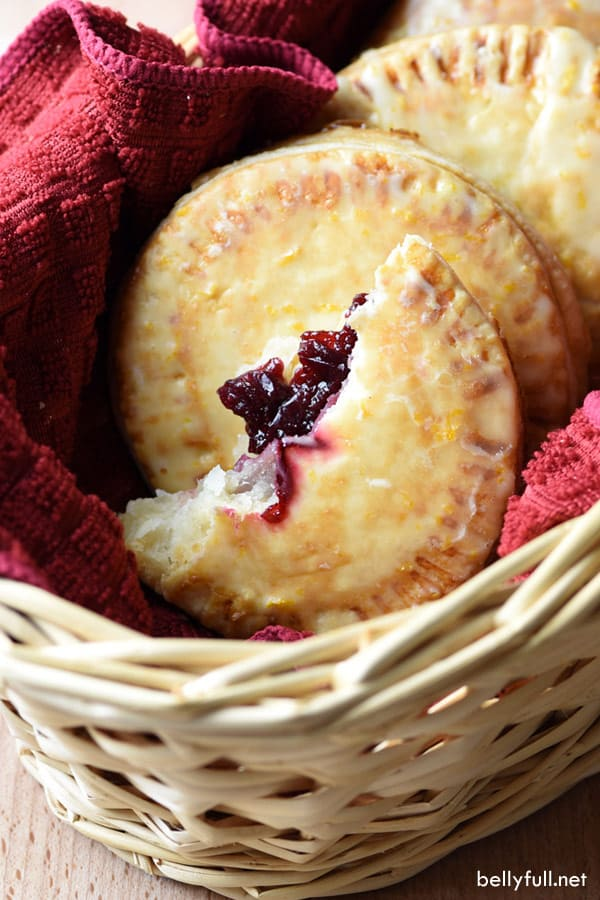 picture of a cranberry hand pie broken in half in a basket