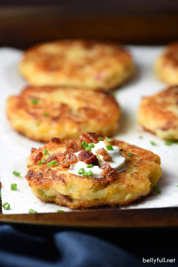picture of a mashed potato cake with sour cream, bacon, and chives