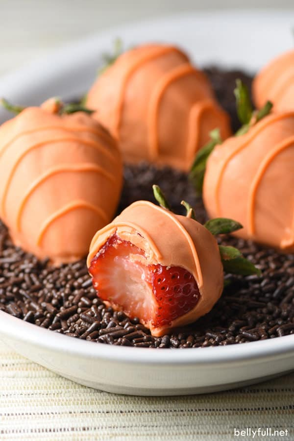 strawberry coated in orange chocolate to look like a carrot with a bite taken
