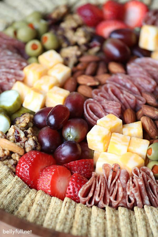 Charcuterie board with crackers, fresh fruit, cheese, and nuts