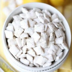 overhead picture of lemon muddy buddies in white bowl with whole lemons and zester on yellow napkin