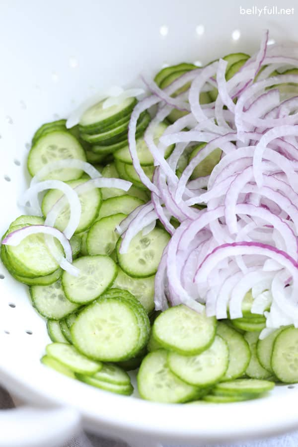 cucumber and red onion in colander