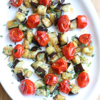 overhead picture of roasted eggplant and cherry tomatoes on white serving plate