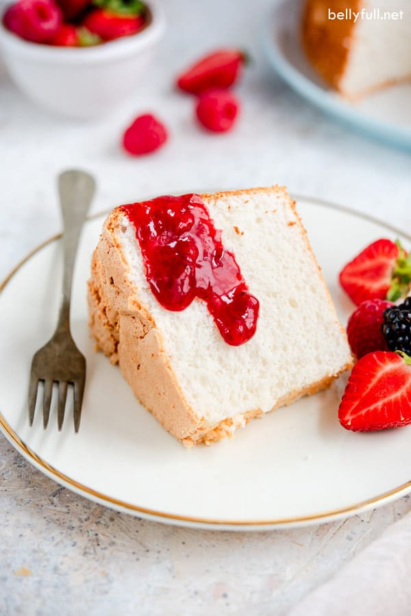 Homemade Angel Food Cake slice on white plate with fork and strawberry sauce