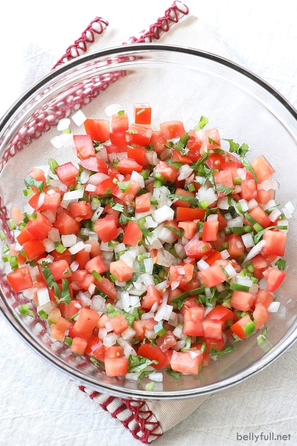 Diced tomato, white onion, jalapeno, and cilantro mixed together in clear bowl