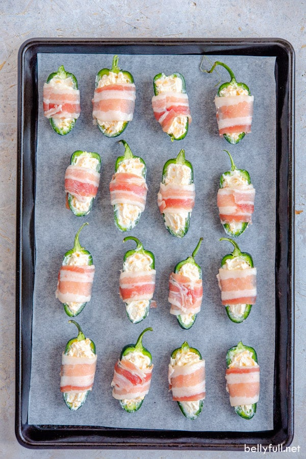 jalapeno peppers stuffed with cream cheese, wrapped in bacon on baking sheet