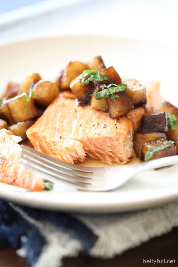 flaked broiled salmon with caramelized apples on white plate
