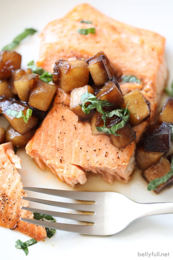 overhead picture of broiled salmon with caramelized apples and fresh snipped basil