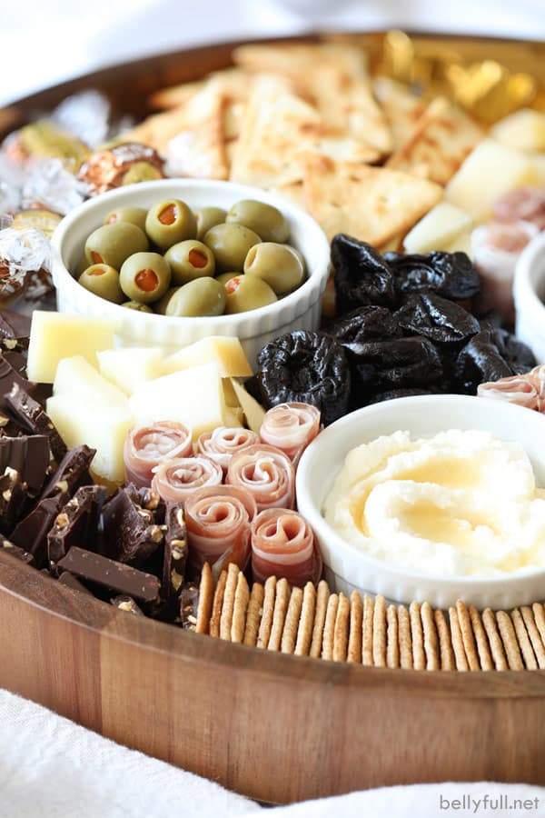 Charcuterie Board with prunes, olives, prosciutto, ricotta, and crackers
