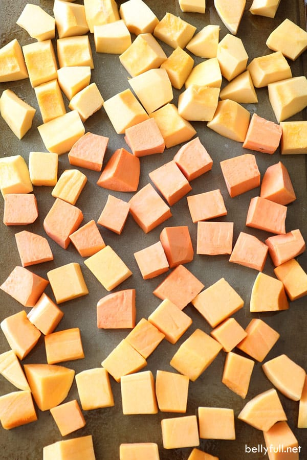 raw cubes of acorn squash, butternut squash, and sweet potato in roasting pan