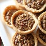 mini pecan pies stacked on a plate