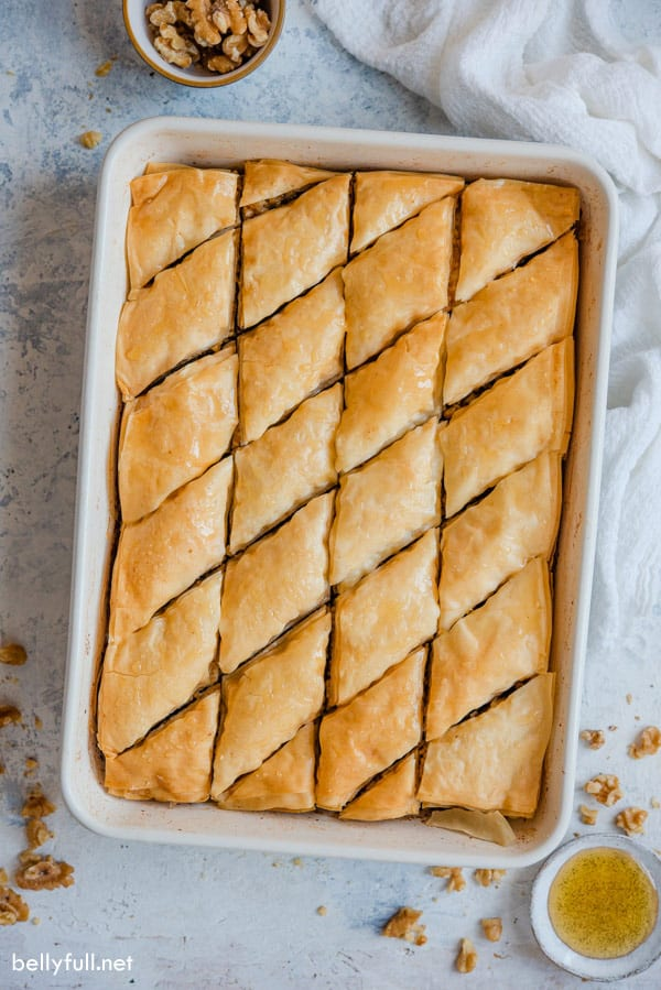 overhead picture of cooked Baklava in baking dish cut into triangle pattern
